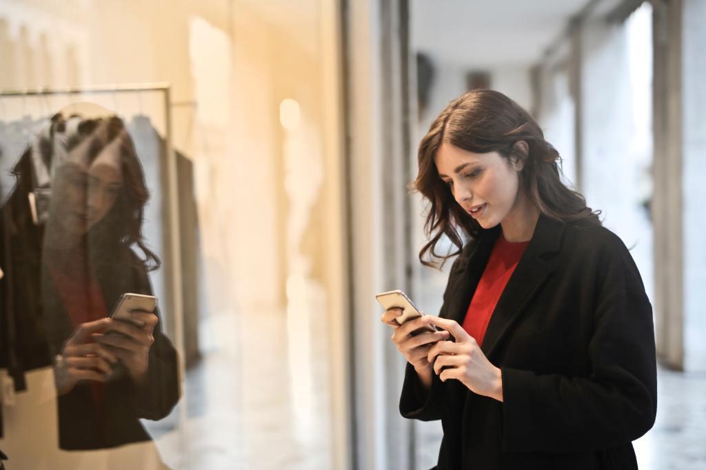 une cliente consulte son smartphone devant une vitrine