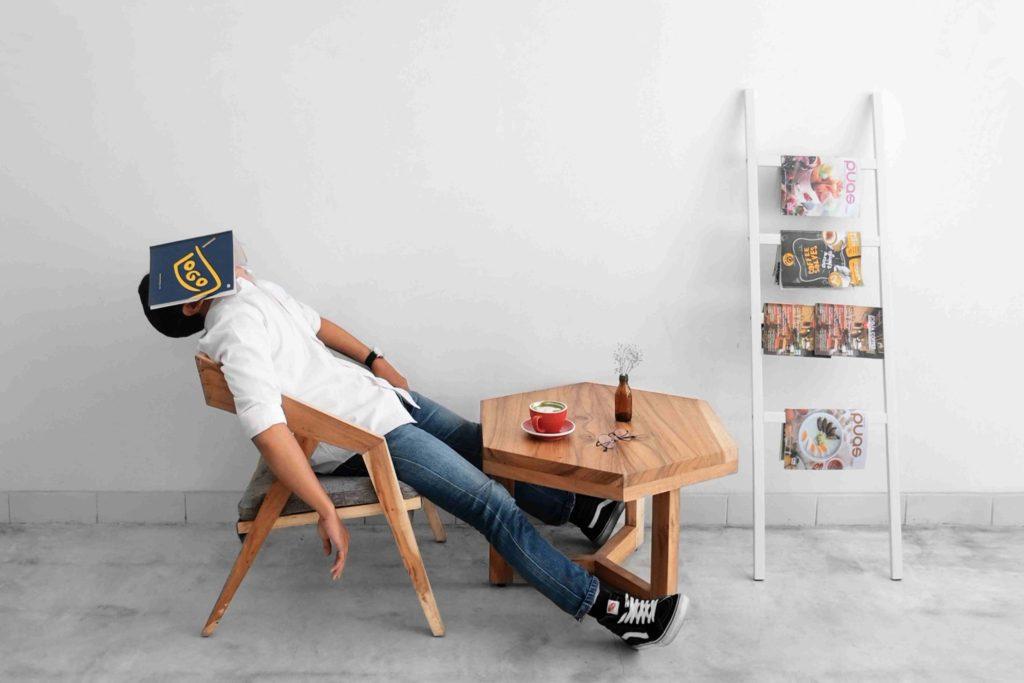 le brown out, un salarié a bout dans une salle de pause avec un magazine sur le visage